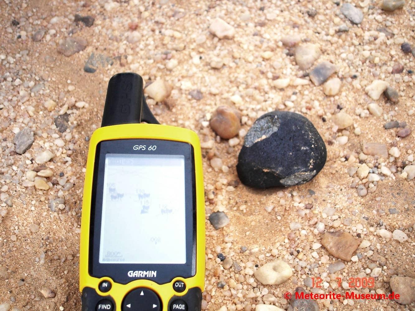 Schwarzer Almahata Sitta Individuum Meteorit mit teilweise abgeplatzter Schmelzkruste neben GPS-Gerät auf dem Wüstensandboden