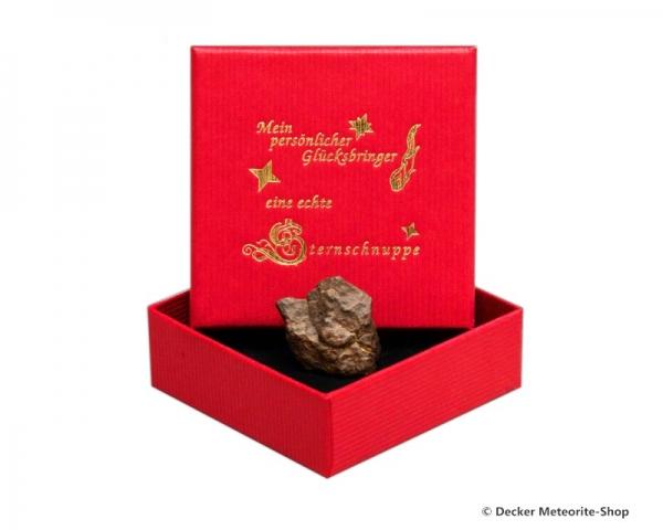 Glücksbringer-Sternschnuppe als Steinmeteorit in roter Glücksbringer-Geschenkbox