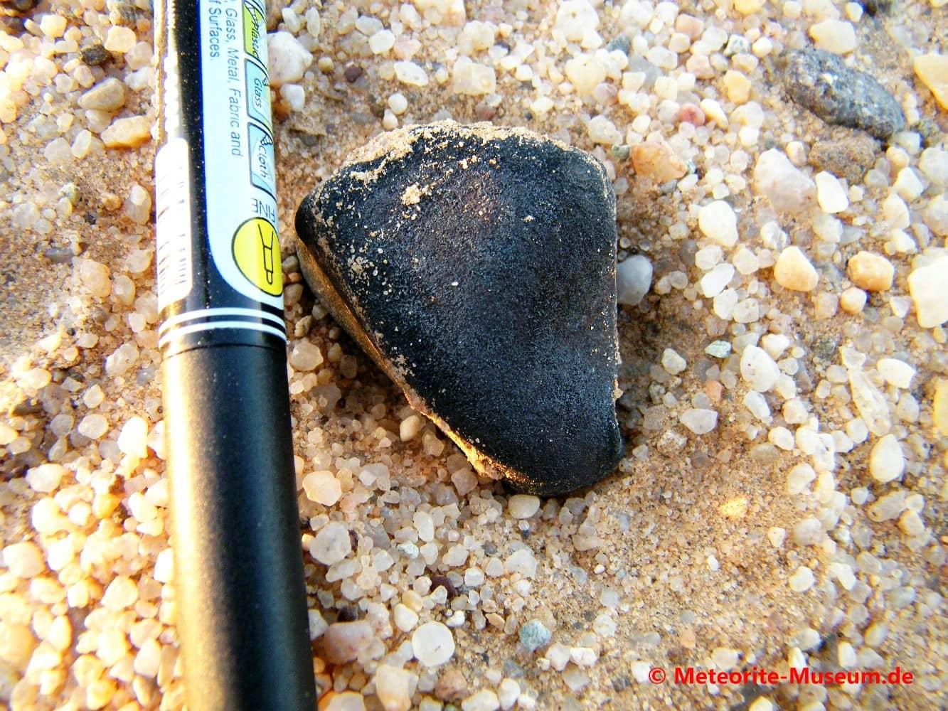 Almahata Sitta Individuum Meteorit mit schwarzer Schmelzkruste auf dem Wüstensandboden