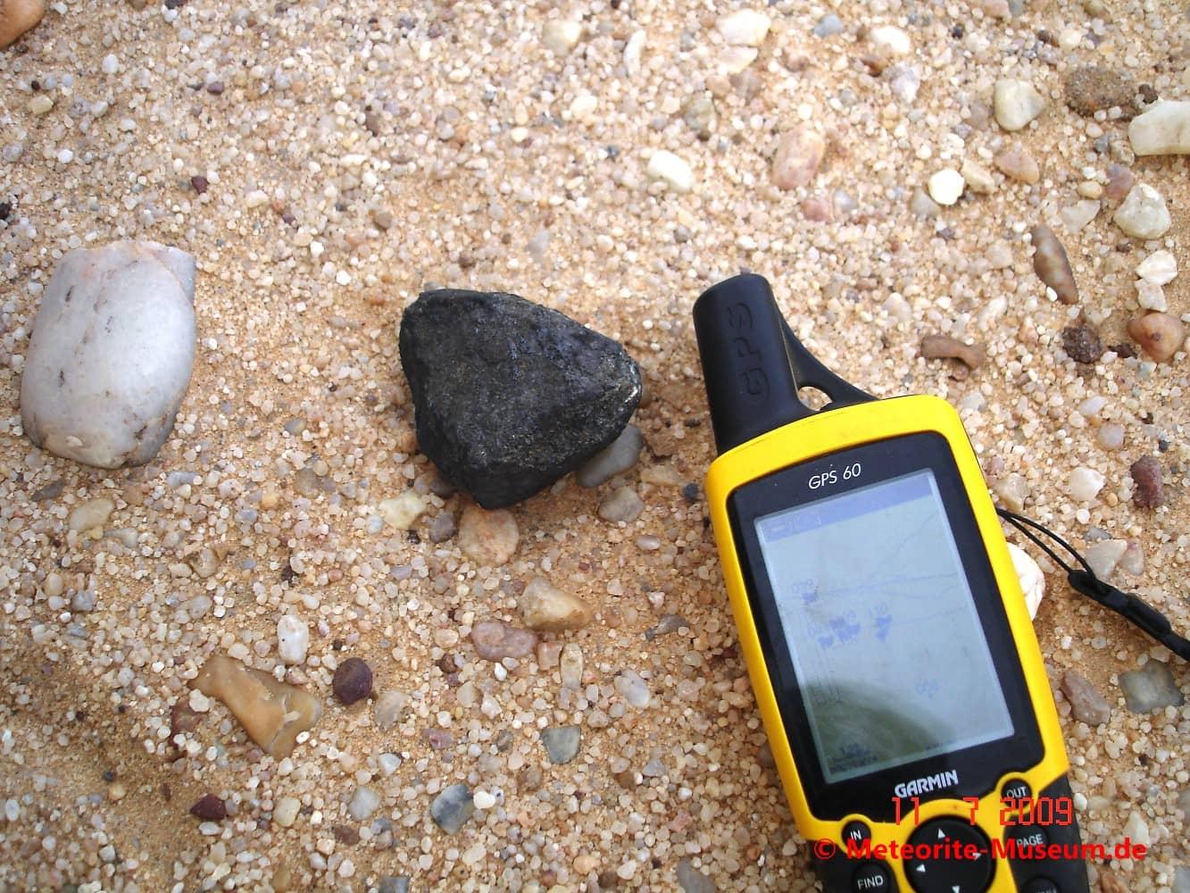 Komplett erhaltener Almahata Sitta Individuum Meteorit mit vollständig umschlossener und schwarzer Schmelzkruste neben GPS-Gerät auf dem Wüstensandboden