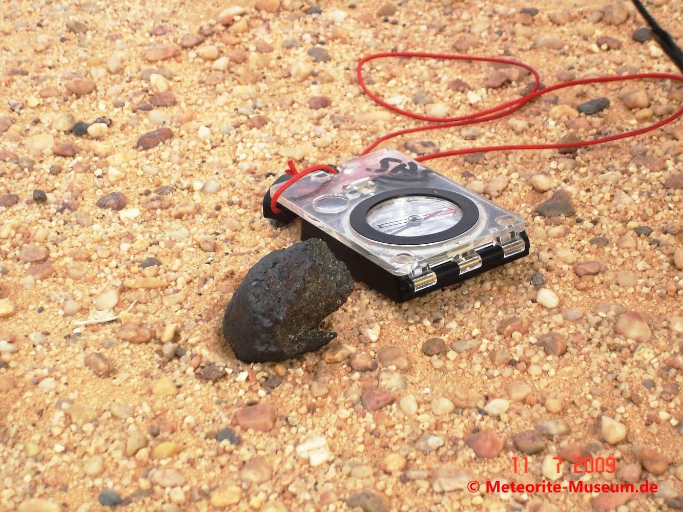 Almahata Sitta Meteorit Bruchstück neben einem Kompass auf dem Wüstensandboden