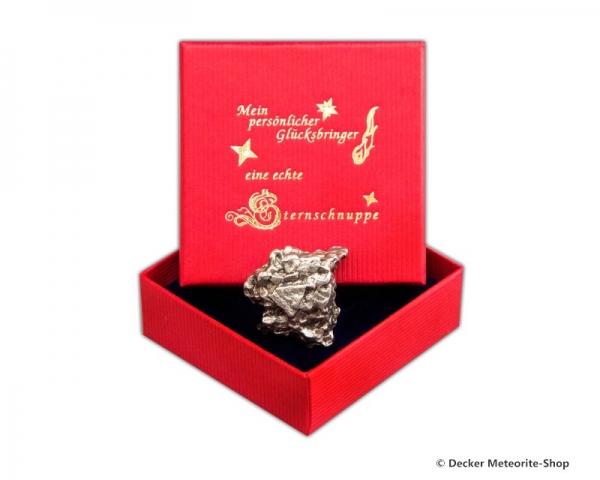 Glücksbringer-Sternschnuppe als Eisenmeteorit in roter Glücksbringer-Geschenkbox