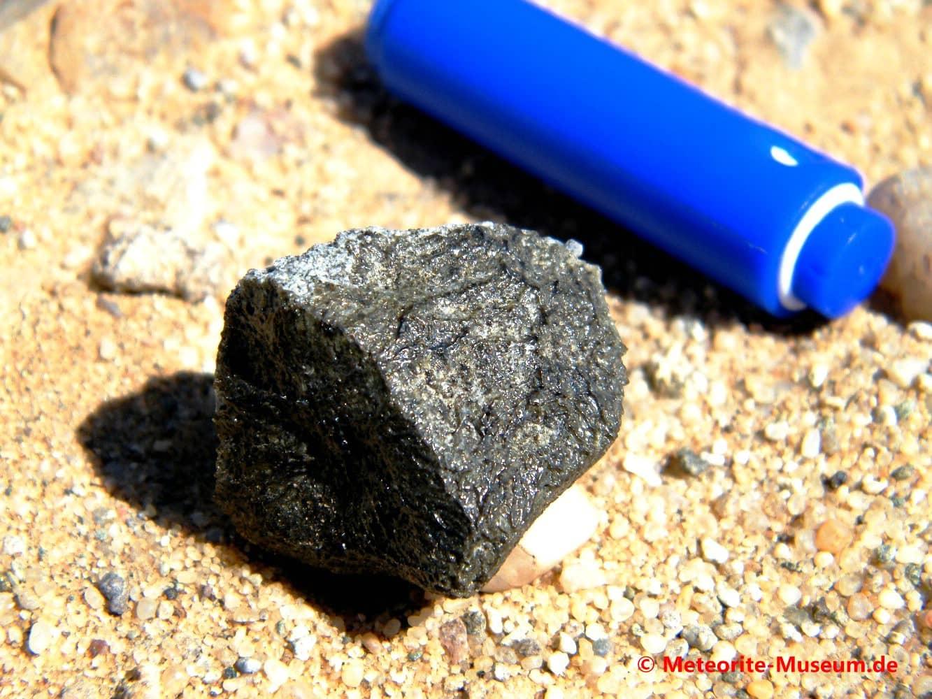 Almahata Sitta Meteorit Bruchstück mit schwarz-grüner Schmelzkruste und GPS-Gerät