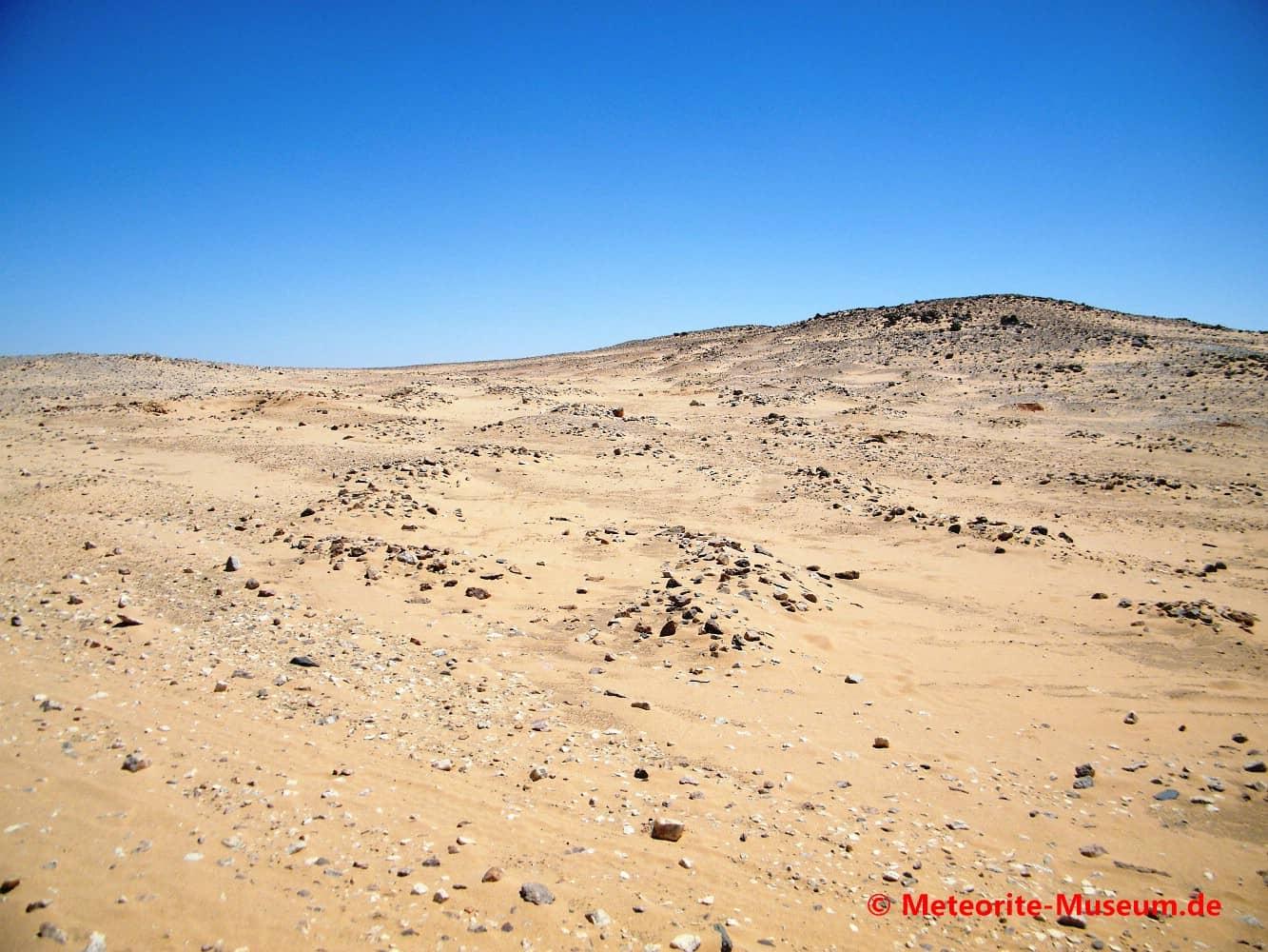 Die nubische Wüste mit Steinfelder, Hügel und tief blauem Himmel nahe der Almahata Sitta Meteoriten-Fundstelle
